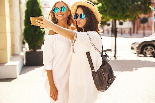 Due giovani donne alla moda hippy donne castane e bionde modellano nel giorno soleggiato dell'estate in vestiti bianchi dei pantaloni a vita bassa che prendono le foto del selfie per i media sociali sul telefono.