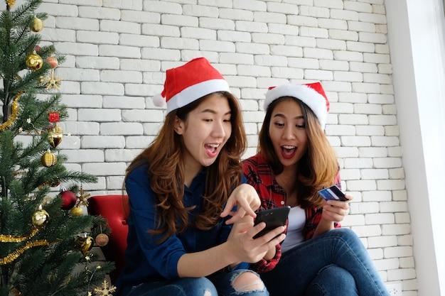 Due giovani donne asiatiche in possesso di smartphone e carta di credito durante lo shopping online