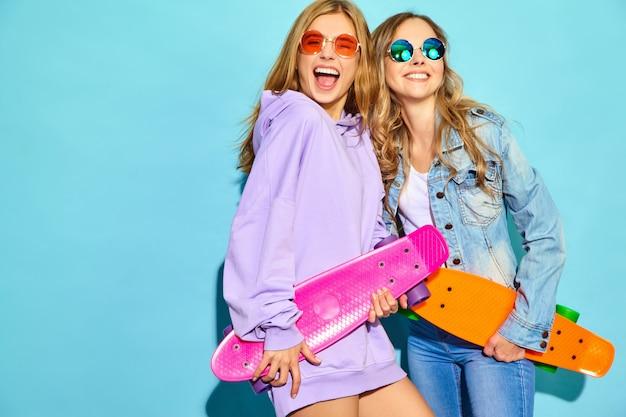 Due giovani donne bionde sorridenti alla moda con i pattini del penny. donne in abiti sportivi estate hipster in posa vicino al muro blu. modelli positivi