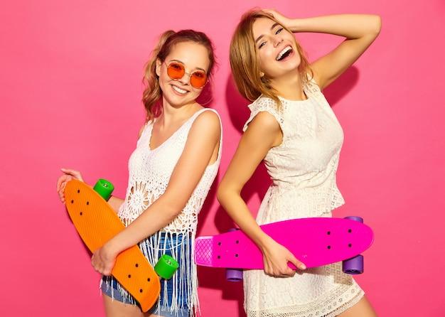Due giovani donne bionde sorridenti alla moda con i pattini del penny. modelli in abiti bianchi hipster estate in posa vicino al muro rosa in occhiali da sole. femmina positiva