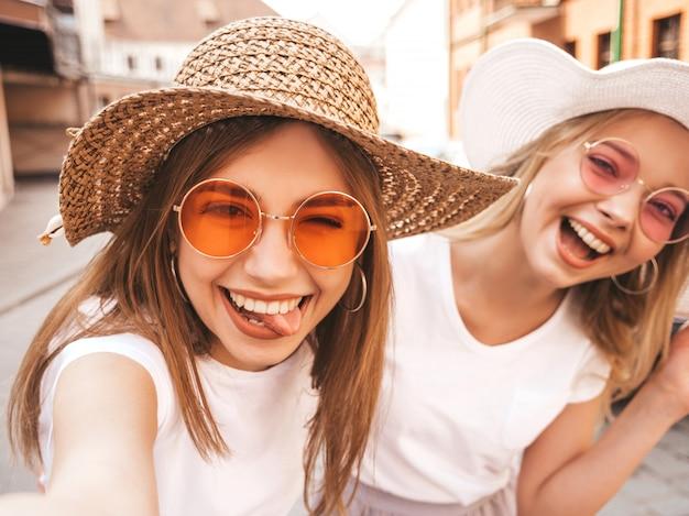 Due giovani donne bionde sorridenti dei pantaloni a vita bassa in maglietta bianca di estate. ragazze che prendono le foto dell'autoritratto del selfie sullo smartphone modelli che posano sul fondo della via la femmina mostra la lingua e le emozioni positive