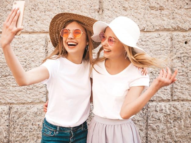 Due giovani donne bionde sorridenti dei pantaloni a vita bassa in maglietta bianca di estate. ragazze che prendono le foto dell'autoritratto del selfie sullo smartphone modelli che posano sul fondo della via la femmina mostra le emozioni positive