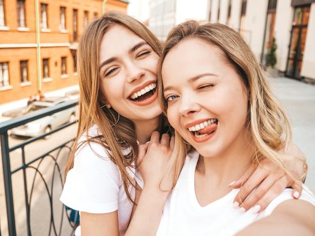 Due giovani donne bionde sorridenti dei pantaloni a vita bassa in vestiti bianchi della maglietta di estate. ragazze che prendono le foto dell'autoritratto del selfie sullo smartphone. lingua femminile che mostra