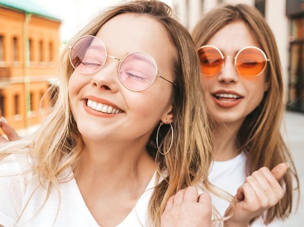 Due giovani donne bionde sorridenti dei pantaloni a vita bassa in vestiti bianchi della maglietta di estate. ragazze che prendono le foto dell'autoritratto del selfie sullo smartphone.