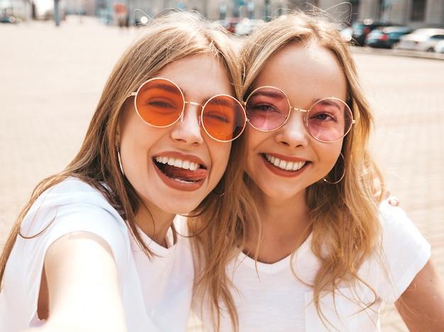 Due giovani donne bionde sorridenti dei pantaloni a vita bassa in vestiti bianchi della maglietta di estate.