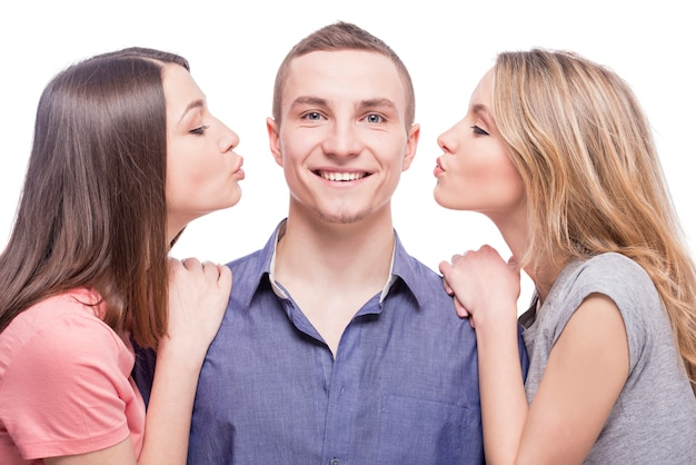 Due giovani donne che baciano per l'uomo.