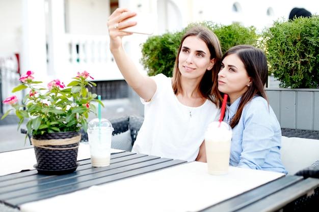 Due giovani donne che bevono il caffè di mattina e che fanno selfie