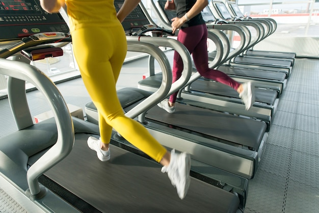 Due giovani donne che corrono sul tapis roulant in palestra