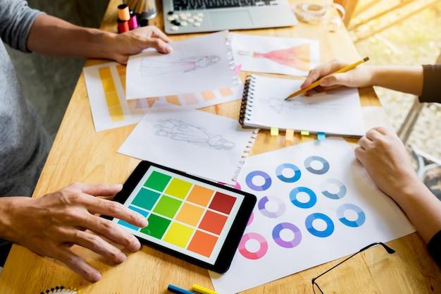 Due giovani donne che lavorano come designer di moda e disegni schizzi e ottiene consigli di tessuto ad un tailor personalizzato