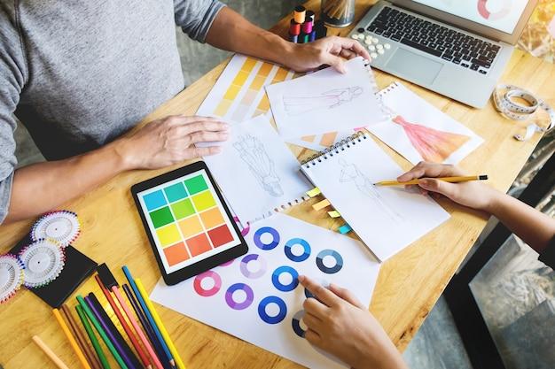 Due giovani donne che lavorano come designer di moda e sketch disegnano e ottengono consigli di tessuto ad un tailor personalizzato