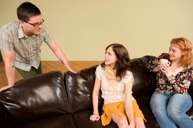 Due giovani donne che parlano all'uomo