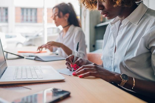 Due giovani donne che scrivono progetto in studio moderno