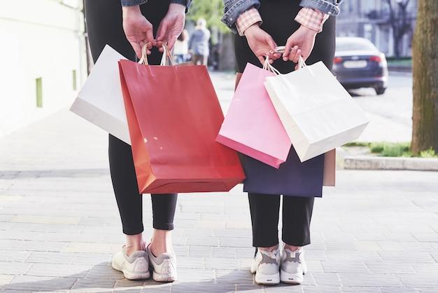 Due giovani donne che trasportano le borse della spesa mentre si cammina per strada dopo aver visitato i negozi.