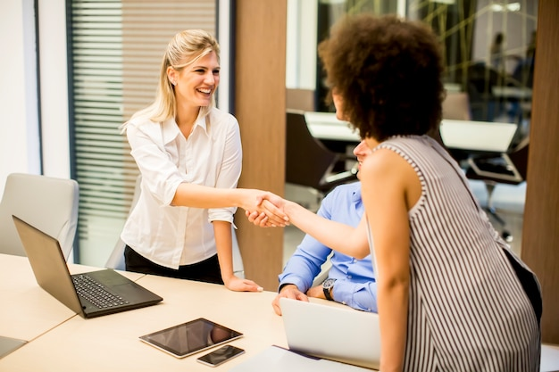 Due giovani donne d'affari si stringono la mano dopo un lavoro ben fatto