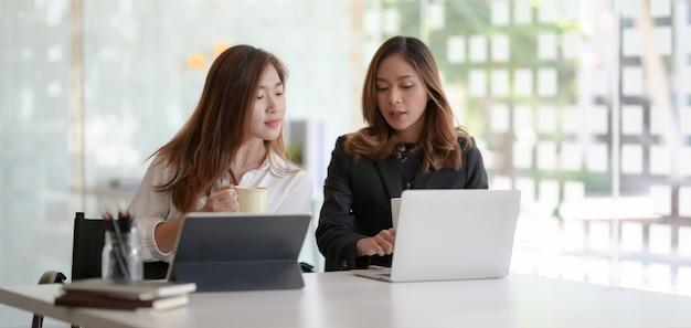 Due giovani donne di affari professionali che consultano insieme il piano di progetto in ufficio moderno