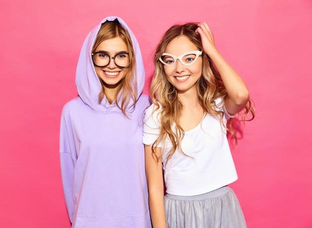Due giovani donne divertenti in bicchieri di carta. concetto intelligente e di bellezza. giovani modelle allegre pronte per la festa. donne in abiti estivi casual isolati sul muro rosa. femmina positiva
