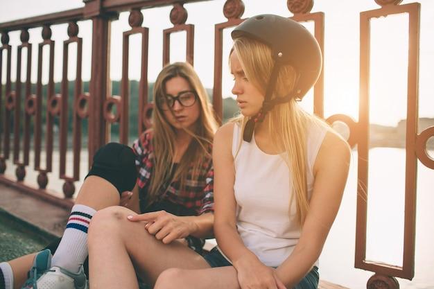Due giovani donne e pattini di rullo sottili e sexy. una femmina ha pattini in linea e l'altra ha pattini quad. le ragazze cavalcano sotto i raggi del sole. lesioni sportive e contusioni.