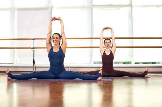 Due giovani donne esili sveglie stanno facendo la posa di yoga mentre stavano in una palestra luminosa vicino ad una grande finestra.