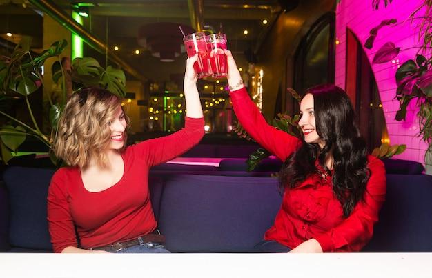 Due giovani donne in abiti rossi bevono cocktail e festeggiano in un locale notturno o in un bar.