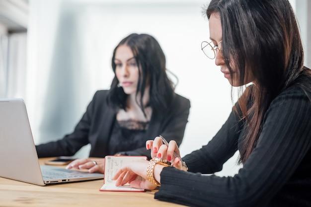 Due giovani donne interne utilizzando il computer portatile