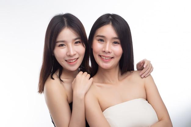 Due giovani donne rimasero felici insieme da dietro.