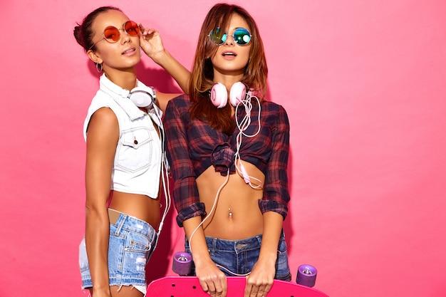 Due giovani donne sorridenti alla moda del brunette con i pattini del penny. modelli in abiti hipster estate in posa vicino al muro rosa in studio in occhiali da sole con le cuffie