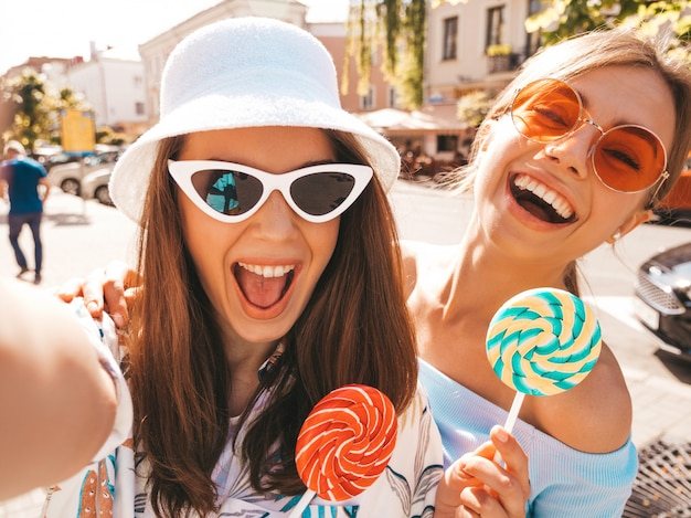 Due giovani donne sorridenti dei pantaloni a vita bassa in vestiti casuali di estate.