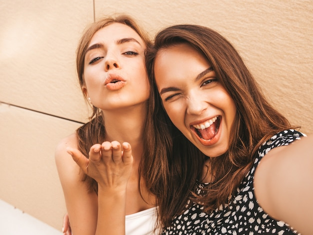 Due giovani donne sorridenti dei pantaloni a vita bassa in vestiti di estate.