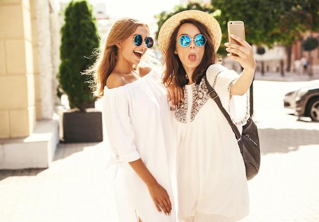 Due giovani donne sorridenti hippie brunette donne e modelli biondi in abito bianco hipster estate prendendo foto selfie per social media sul telefono. sorpresa viso, emozioni,