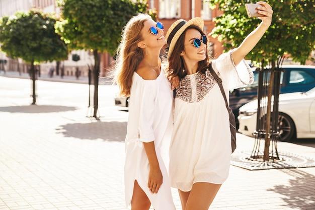 Due giovani donne sorridenti hippie donne castane e bionde modellano nel giorno soleggiato dell'estate in vestiti bianchi dei pantaloni a vita bassa che prendono le foto del selfie per i media sociali sul telefono.