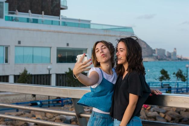 Due giovani donne stanno prendendo un selfie con una macchina fotografica istantanea sulla costa