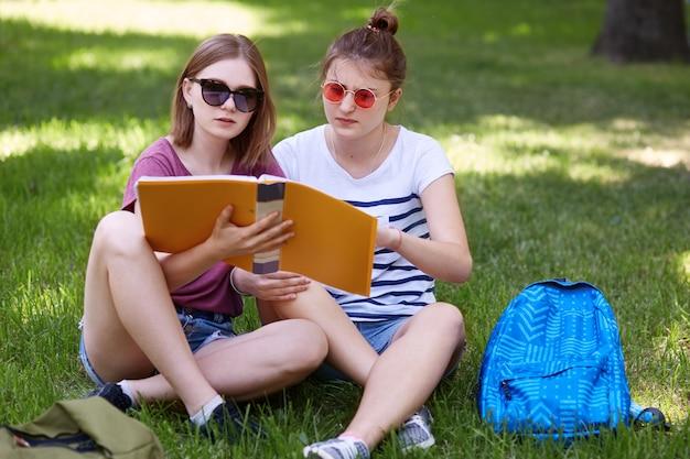 Due giovani donne studiano insieme nel parco, indossano abiti casual e occhiali da sole, leggono abstract mentre si preparano per un seminario all'università, hanno concentrato le espressioni facciali. studenti e istruzione
