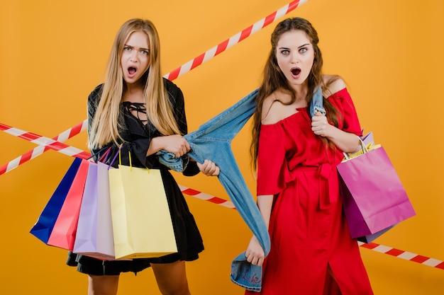 Due giovani e belle ragazze sorprese che combattono sopra le paia dei jeans con i sacchetti della spesa variopinti e nastro adesivo isolato sopra giallo