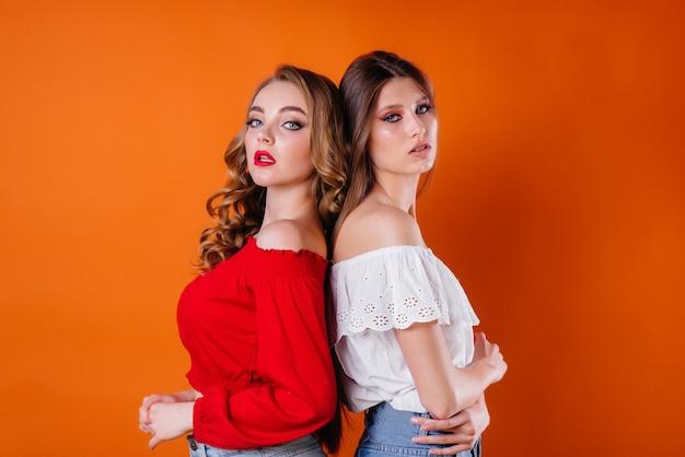 Due giovani e ragazze mostrano emozioni e sorrisi nello studio onn arancione. ragazze per la pubblicità.
