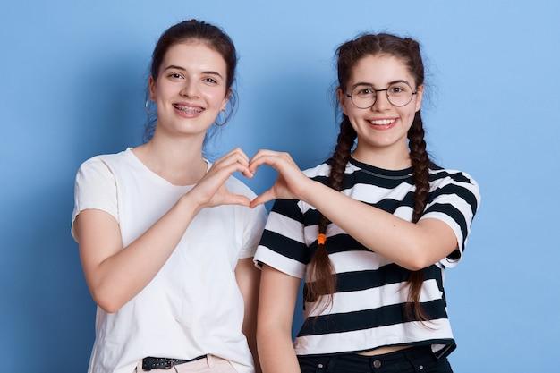 Due giovani femmine sorridenti in abbigliamento casual che fa il cuore usando le loro mani