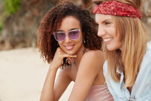 Due giovani fidanzate felici hanno relazioni omosessuali, godono dell'aria fresca all'aperto mentre trascorrono il tempo libero sulla spiaggia sabbiosa, fanno viaggi durante l'estate e le buone condizioni meteorologiche. coppia di donne.
