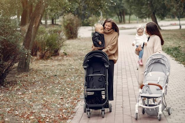 Due giovani madri che camminano in un parco in autunno con le carrozze