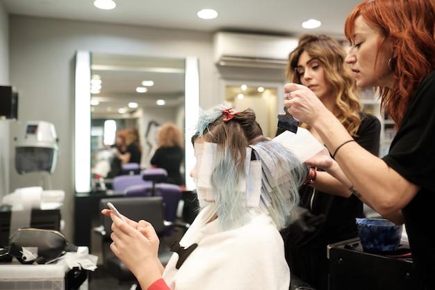 Due giovani parrucchieri che tingono capelli del cliente femminile mentre legge il suo telefono cellulare