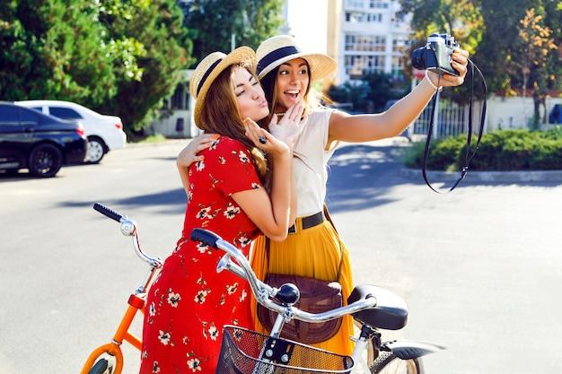 Due giovani ragazze abbastanza alla moda che posano vicino alle biciclette retro luminose dei pantaloni a vita bassa e che fanno autoritratto