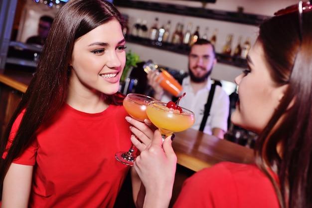 Due giovani ragazze carine bevono cocktail in un locale notturno o in un bar, si divertono, sorridono e parlano con il barista