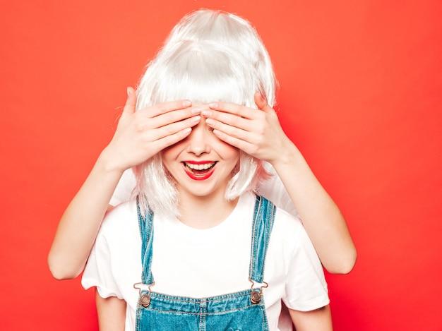 Due giovani ragazze sexy hipster in parrucche bianche e labbra rosse. belle donne alla moda in abiti estivi. modelle vivaci in posa vicino al muro rosso in studio. coprendosi gli occhi e abbracciando da dietro