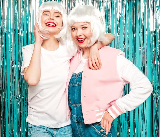 Due giovani ragazze sexy hipster in parrucche bianche e labbra rosse. belle donne alla moda in estate vestiti divertendosi