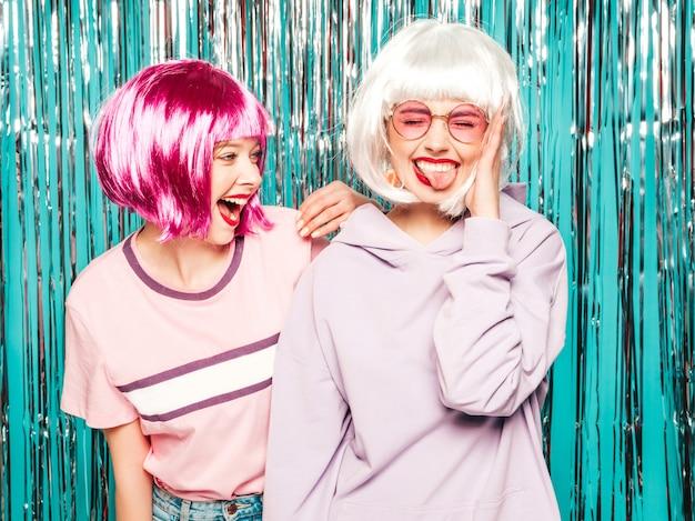 Due giovani ragazze sexy hipster in parrucche e labbra rosse. belle donne alla moda in abiti estivi divertirsi