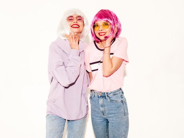 Due giovani ragazze sexy hipster sorridenti in parrucche e labbra rosse. belle donne alla moda in abiti estivi. modelli gratuiti in posa vicino al muro bianco in studio impazzendo e abbracciando