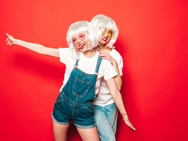 Due giovani ragazze sorridenti sexy dei pantaloni a vita bassa in parrucche bianche e labbra rosse belle donne d'avanguardia in vestiti di estate modelli liberi che posano vicino alla parete rossa di estate dello studio in occhiali da sole