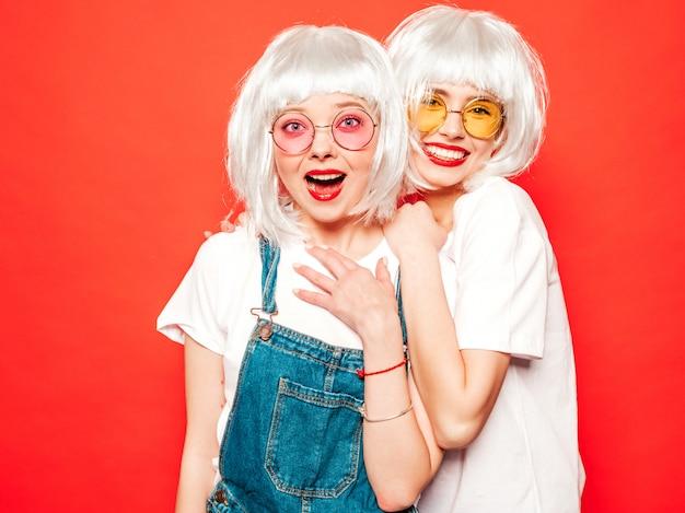 Due giovani ragazze sorridenti sexy dei pantaloni a vita bassa in parrucche bianche e labbra rosse belle donne d'avanguardia in vestiti di estate modelli liberi che posano vicino alla parete rossa nell'estate dello studio che impazzisce