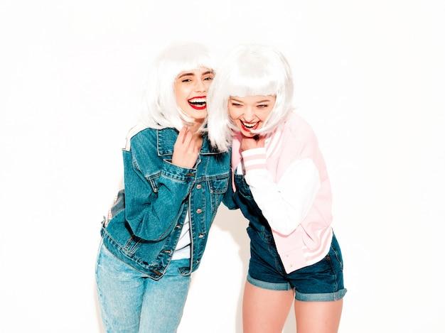 Due giovani ragazze sorridenti sexy dei pantaloni a vita bassa in parrucche bianche e labbra rosse che impazziscono