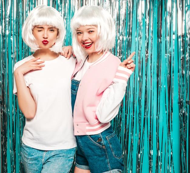 Due giovani ragazze sorridenti sexy dei pantaloni a vita bassa in parrucche bianche e labbra rosse le belle donne d'avanguardia di estate copre l'estate