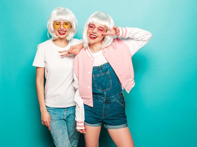 Due giovani ragazze sorridenti sexy dei pantaloni a vita bassa in parrucche e labbra rosse belle donne d'avanguardia in vestiti di estate modelli liberi che posano vicino alla parete blu in estate dello studio mostra la lingua e il segno di pace
