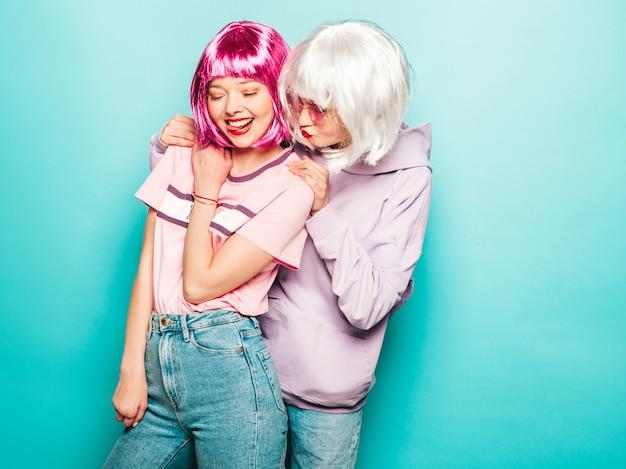 Due giovani ragazze sorridenti sexy dei pantaloni a vita bassa in parrucche e labbra rosse belle donne d'avanguardia in vestiti di estate modelli liberi che posano vicino alla parete blu in studio che impazzisce e che abbraccia